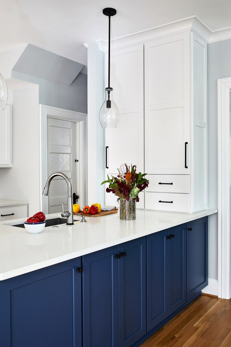 blue kitchen cabinets with black knobs, white marble counter tops and white cabinets with pull handles