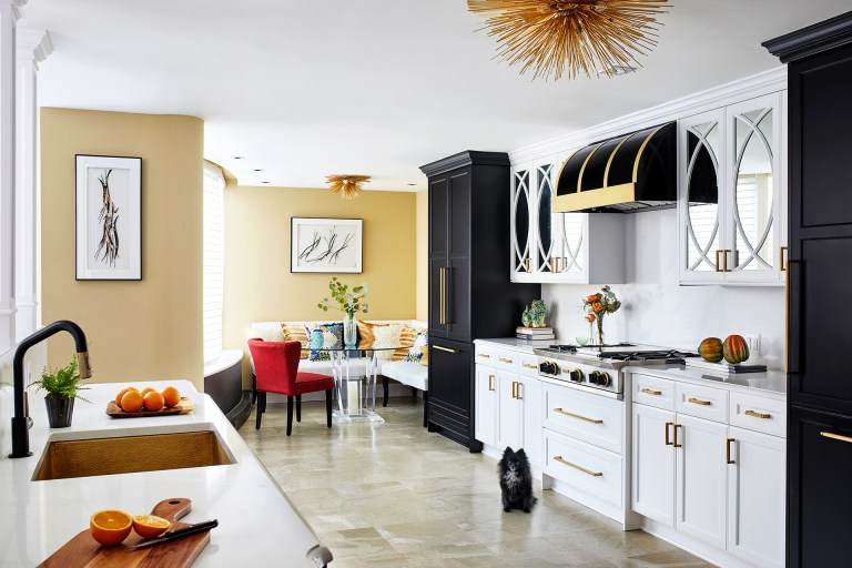 white and gold kitchen with black range hood, cabinets with brass pulls paired with marble countertops