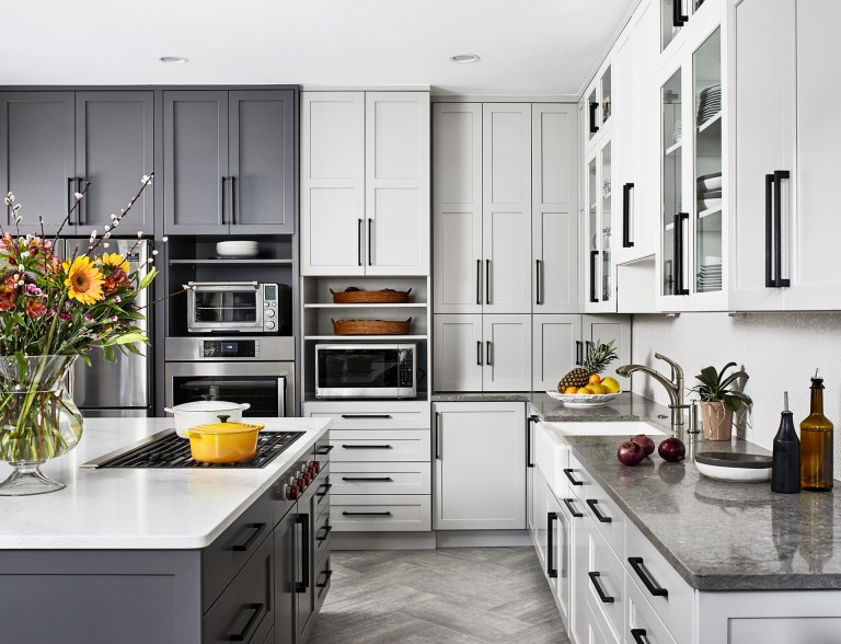 kitchen island with stove top and grey base, grey and white cabinets with black pull handles two open shelves
