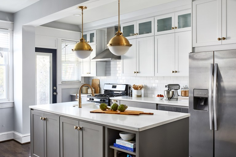 grey cabinetry on the island with white tall cabinets and gold knobs with stainless steel appliances