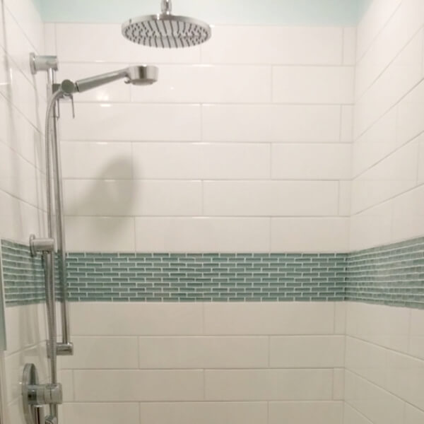 clean white spa shower with blue glass accent tiles