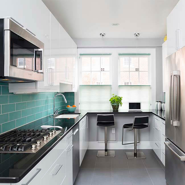 galley kitchen with Teal tile, white cabinets, stainless steel appliences, and dark quartz counters Halifax Case Design