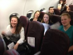 Trying to keep our spirits up while fanning ourselves on the plane!