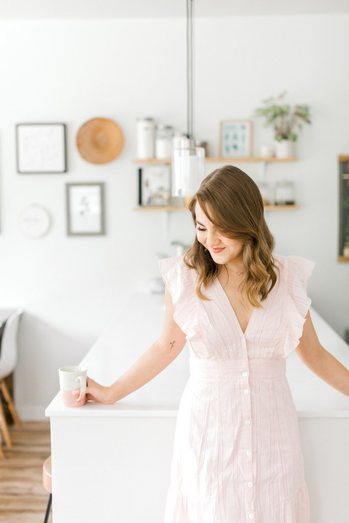 Woman in pink dress holding coffee mug standing in kitchen looking down to the side.