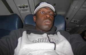 A shot of me in a hoodie aboard a plane to Europe