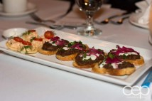 A plate with shrimp salad on rice cakes and pulled pork bruschetta at Mysteriously Yours... Mystery Dinner Theatre