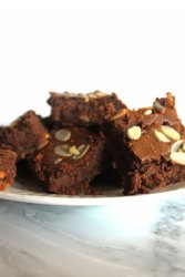 White plate full of brownies topped chocolate chips and slivered almonds