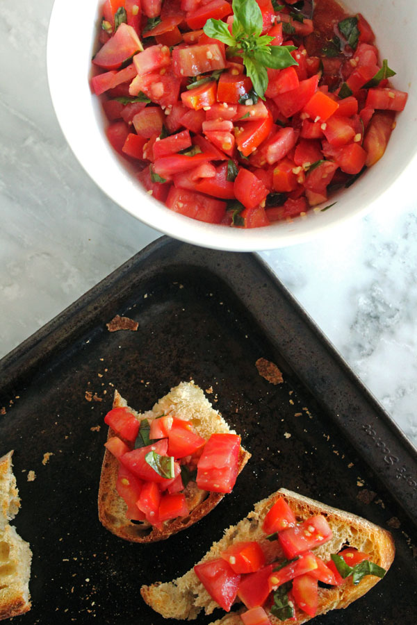 Toasted sourdough topped with bruschetta on a black cookie sheet next to a bowl of bruschetta.