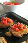 Baking sheet with toasted sourdough topped with bruschetta