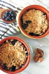 Two bowls of fig and blueberry cobbler with fresh cut figs and a spoonful of fresh blueberries