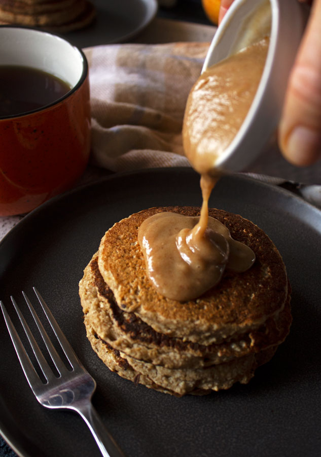 Caramel apple pancakes on a plate with date caramel sauce being poured on the pancakes.