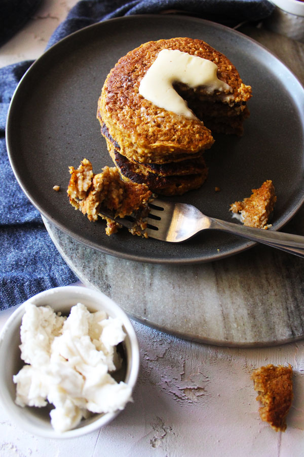 Pumpkin pancakes topped with vegan butter.