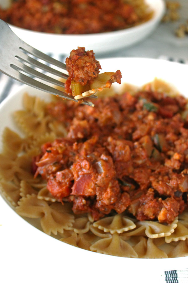 """Pasta and walnut and tofu """"meat"""" bolognese sauce on a fork."""