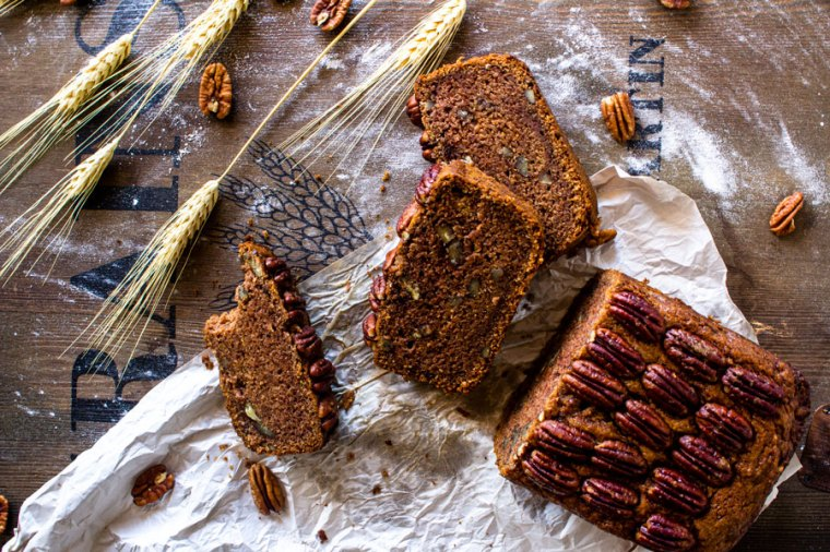 Slices of pecan pie quick bread on a wooden cutting board with wheat and pecan halves.