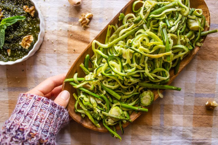 Roasted green vegetables (asparagus, Brussel's sprouts, and zucchini spirals) on a wooden platter being set on a table next to a bowl of vegan walnut pesto.