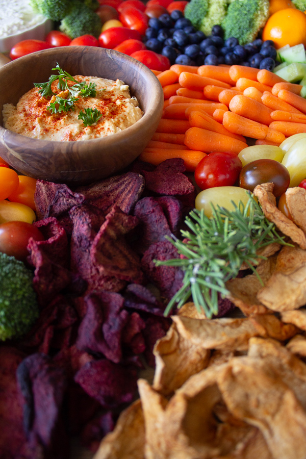 Charcuterie board with fresh vegetables, fresh & dried fruits, chips, hummus, and vegan cheese.
