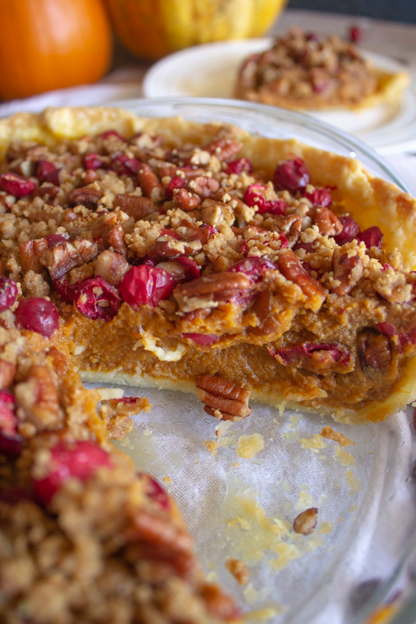 A vegan pumpkin pie with cranberry pecan streusel topping missing 1 slice which is on a white plate in the background.
