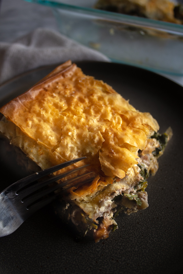 Close up of vegan walnut spanakopita on a black plate being cut with a fork.