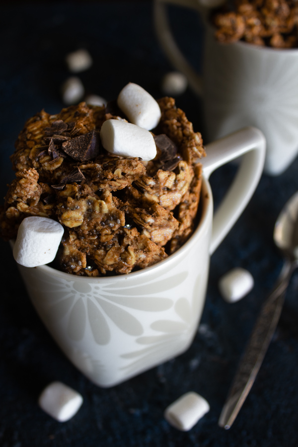 White mug full of hot chocolate granola surrounded by marshmallows and a mug of granola in the background.
