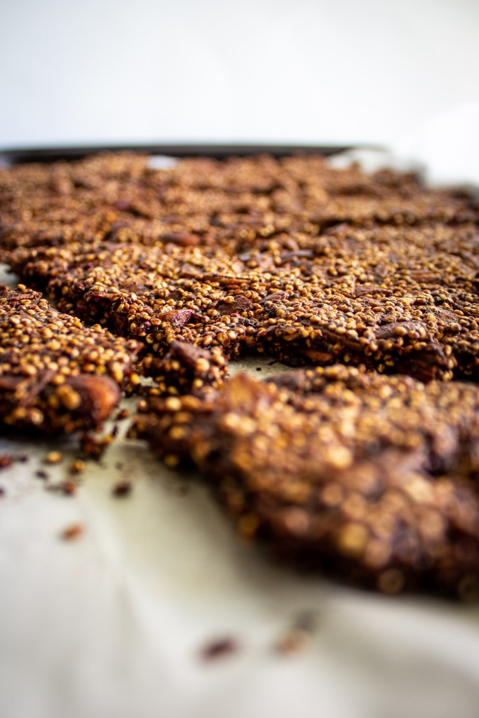 Close up thin mint quinoa granola on parchment paper.