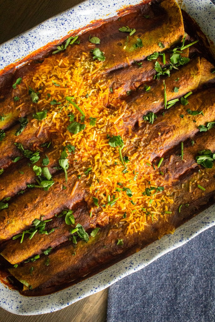 Zucchini and black bean enchiladas in a baking dish topped with fresh chopped cilantro.