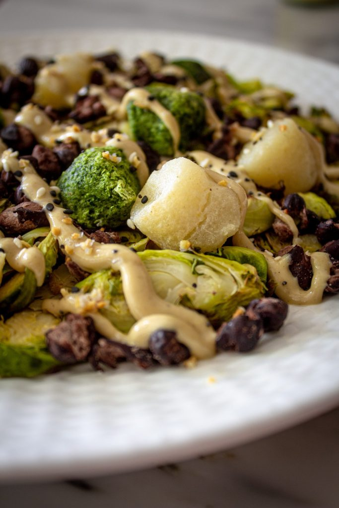 Roasted shaved Brussels spouts, baked black beans, kale and cauliflower gnocchi bowl drizzled with tahini sauce.
