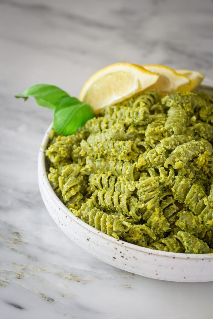 Bowl of seaweed pasta with lemon basil pesto topped with fresh basil and lemon wedges.