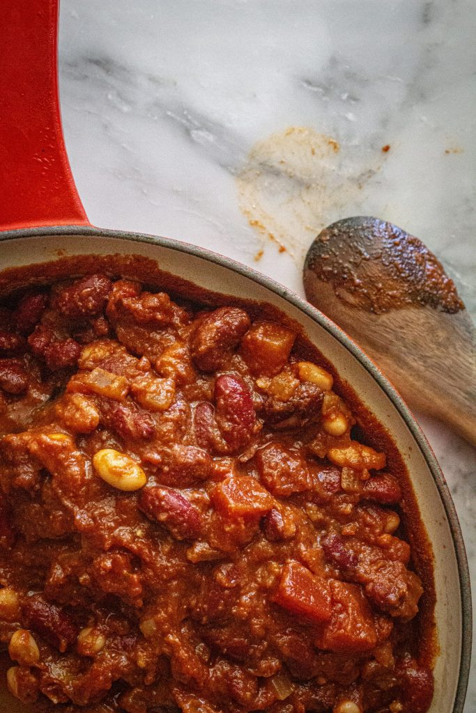 Red cast iron pot full of vegan 2 bean chili and a dirty wooden spoon resting on a white granite countertop.