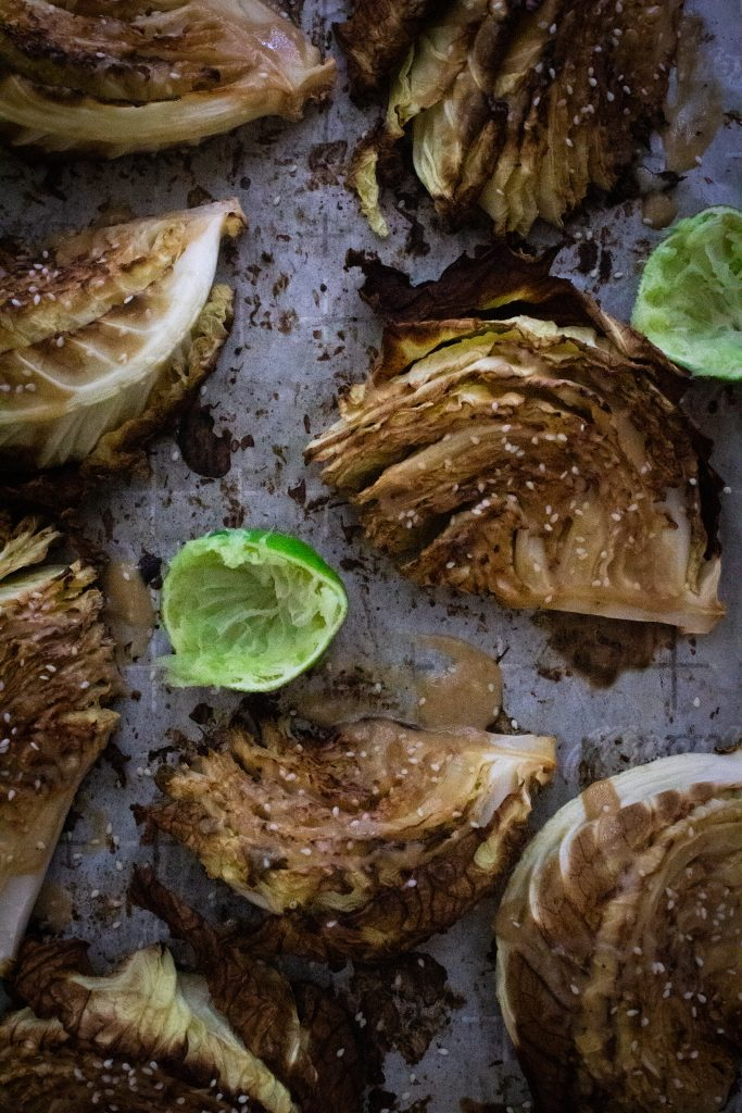 Miso roasted cabbage wedges topped with sesame seeds on parchment paper with lime wedges.