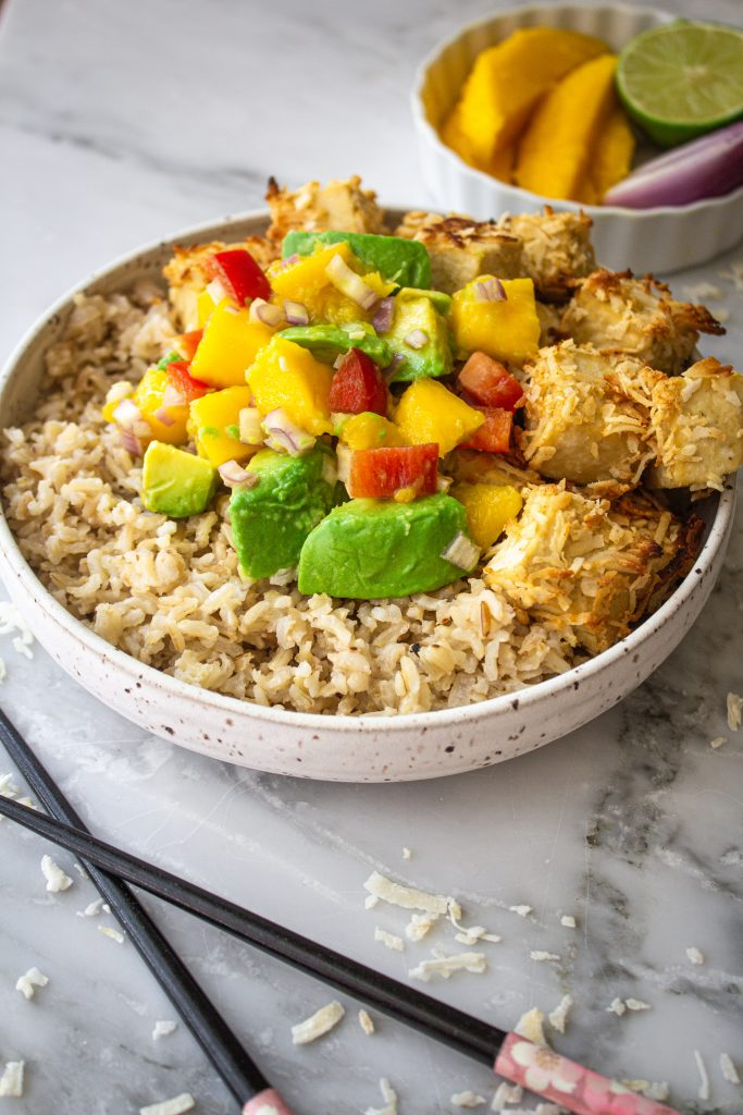 A bowl of coconut rice and coconut crusted tofu topped with mango avocado salsa with a while bowl of mango in the background and chopsticks in the foreground.