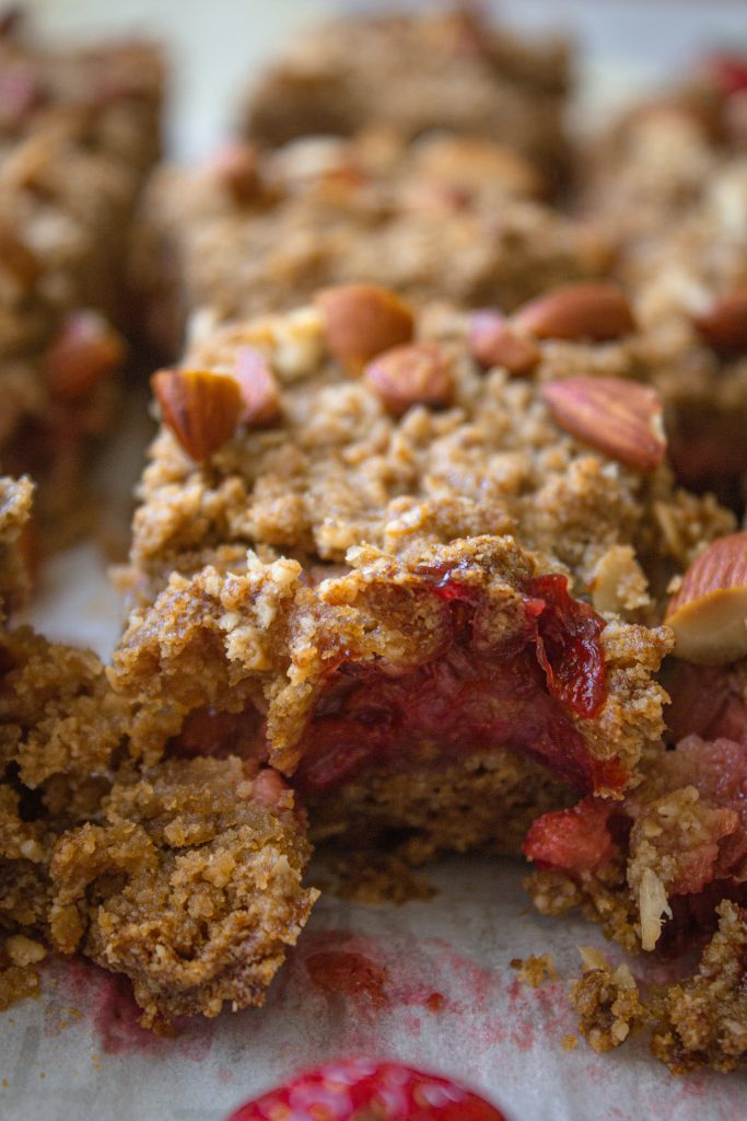 Close up of an almond and strawberry rhubarb crisp bar with a bite missing.