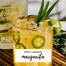 Glass of spicy mango margarita garnished with lime wedge and leaves.