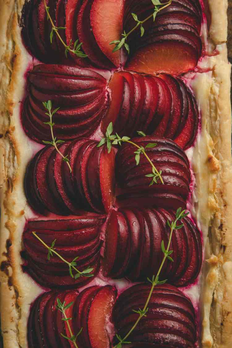 Puff Pastry Plum Tart close up garnished with thyme sprigs