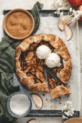 Overhead image of rustic apple galette made with puff pastry. Topped with ice cream and surrounded with ingredients such as sugar, flour, sliced apples and flowers.