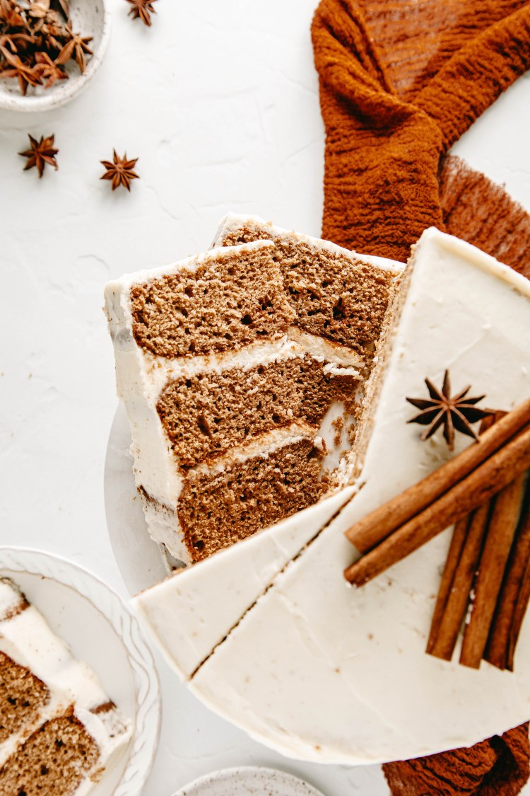 Overhead image of slice spice cake with brown butter frosting. Surrounding by dark orange linen, stars of anise and cinnamon sticks.