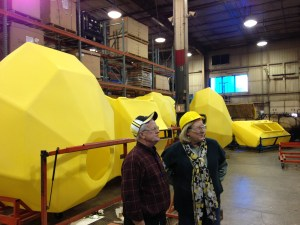 Dave shows Pat the rotary mold machines.  Behind them are the newly-minted yellow tanks in the staging area for the cart assembly line