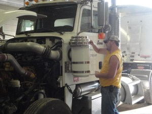 John services the air cleaner on the Peterbilt while he is on the phone with a local mechanic shop.