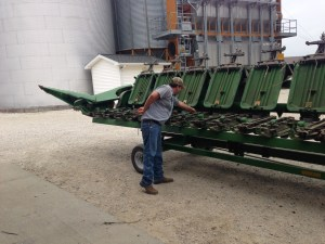 John inspects the gathering chains on the JD 612C corn head.  He adjusts those chains that have too much slack in them.