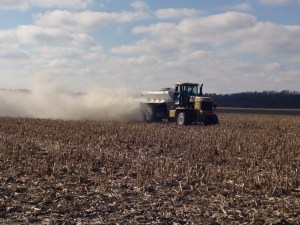 The cloud of lime spread here varies by the map as the spreader truck moves over the field.