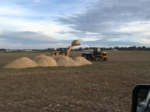 Big trucks dump the raw lime in the field, then it is loaded into the spreader trucks.