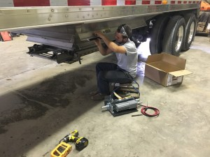 Brandon works on attaching the motorized assembly to the back hopper