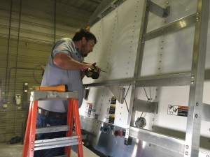 John prepares the front of the trailer to attach  the big control arm