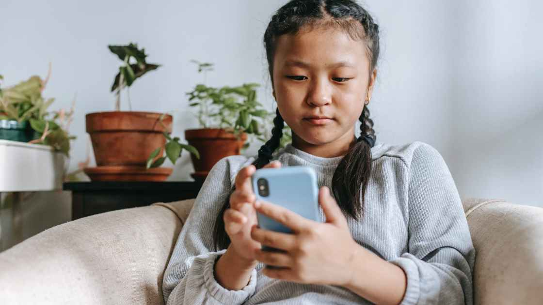 focused ethnic girl with smartphone