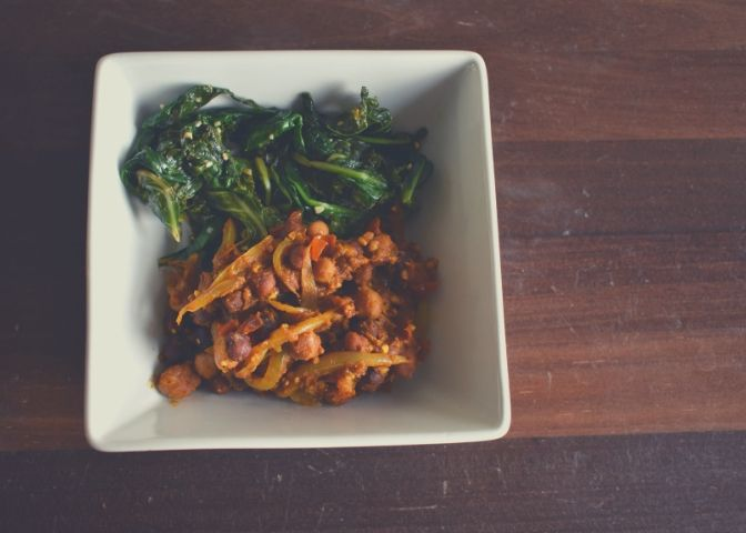 Bowl of chana masala (Indian curried chickpeas) and sautéed spicy and garlic greens