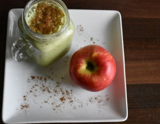 overhead shot of a mug of apple pie protein shake and an apple