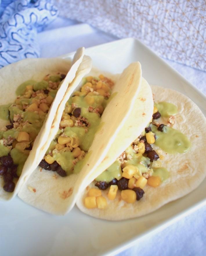 plate of vegan street tacos with black chickpeas, corn and avocado sauce