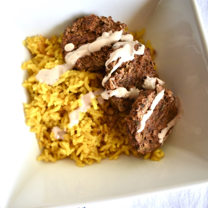 falafel bowl with turmeric rice, tangy garlic tahini, and pinto bean falafel