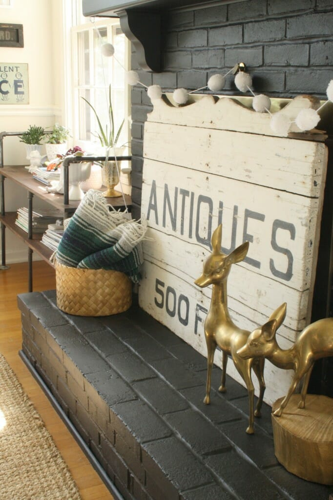 #EclecticallyVintage decorated hearth with brass deer, stump, basket, mexican blanket