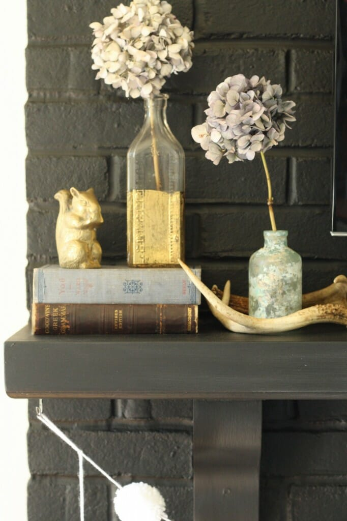 #EclecticallyFall mantle with gold, brass, antlers, and dried hydrangeas