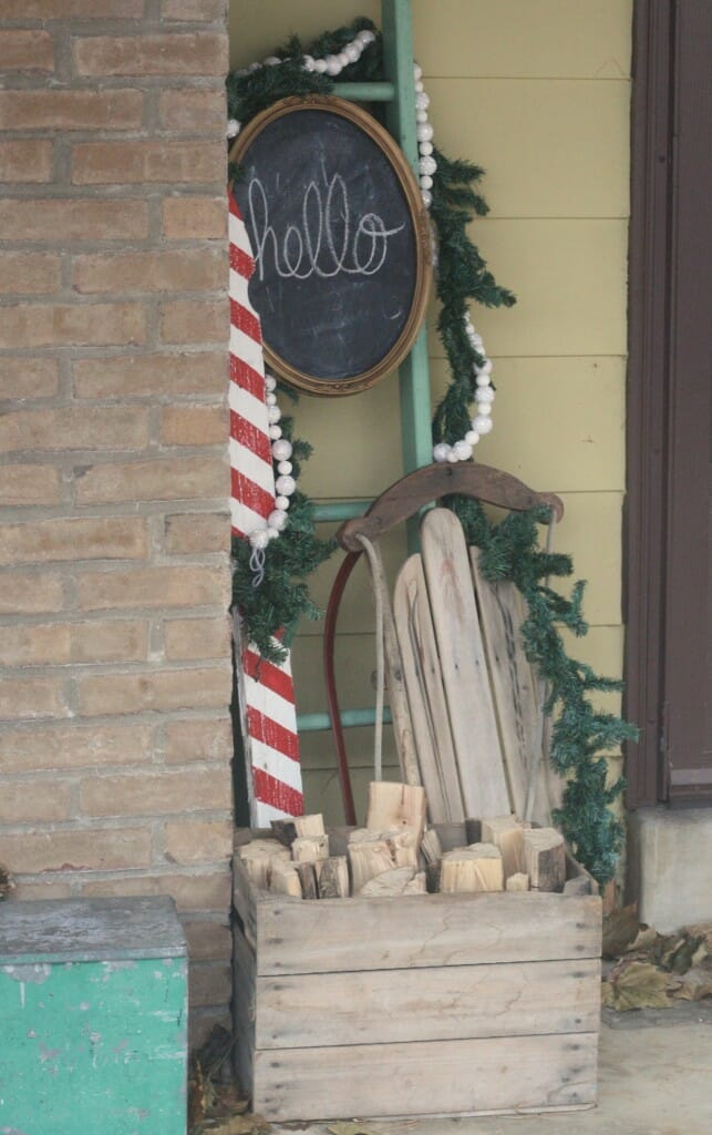 Christmas porch entry with chalkboard, candy cane picket, vnitage ladder, vintage sled, garlands, firewood in crate
